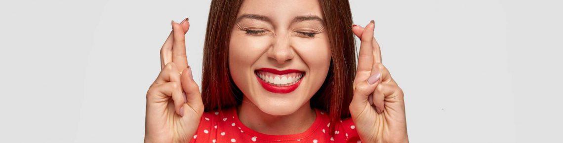 En flicka som bär läs och rött läppstift med korsade fingrar