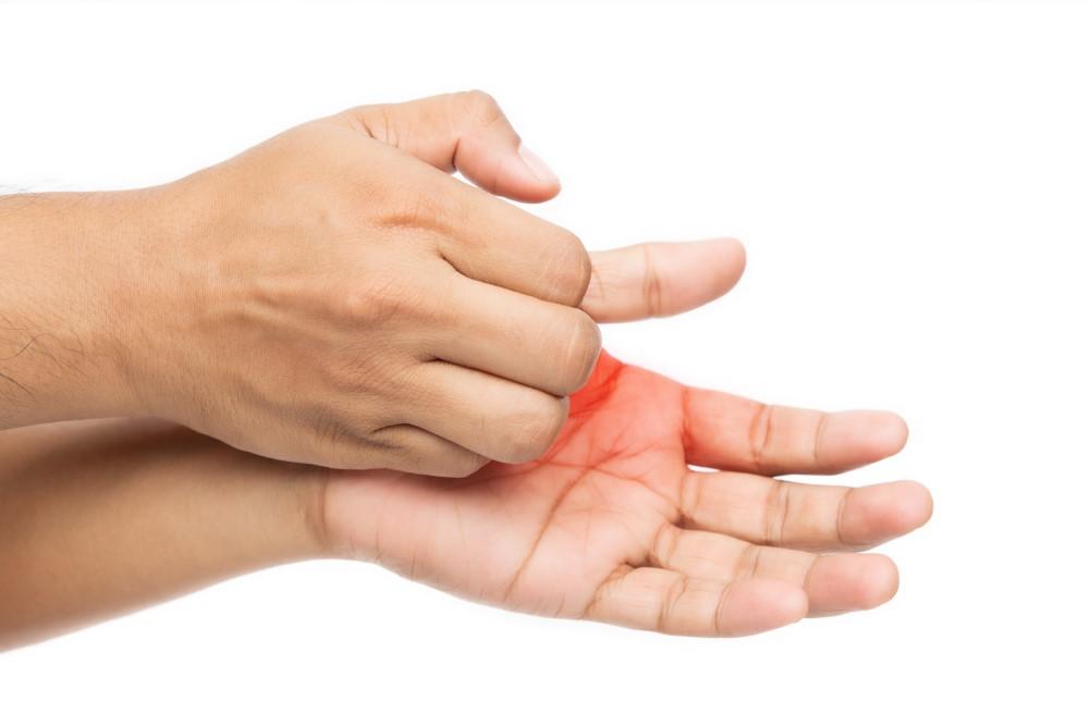 En person kliar sina kliande händer