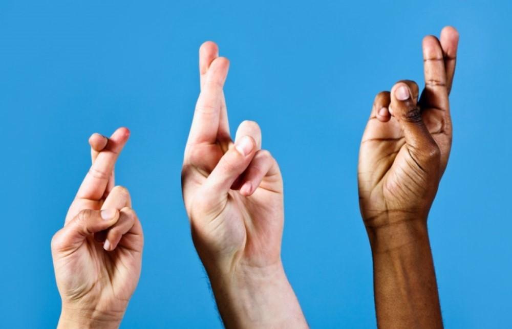 Tre händer med korsade fingrar