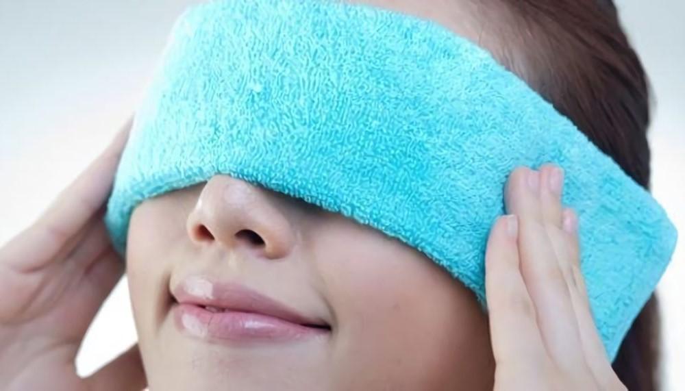 Kvinna med den blå handduken på ögonen är avkopplande hennes ögon