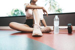 Kvinna sitter i gymmet och koppla av efter övningar