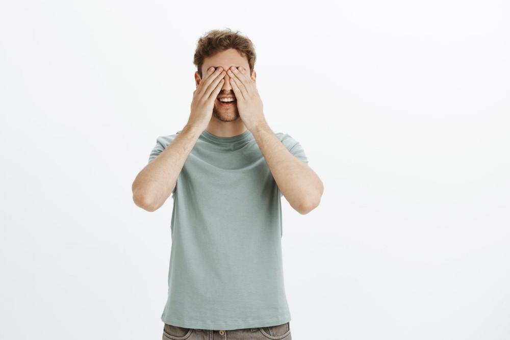 Man bär en grå t-shirt gör palming att vila ögonen efter att ha spelat online casino