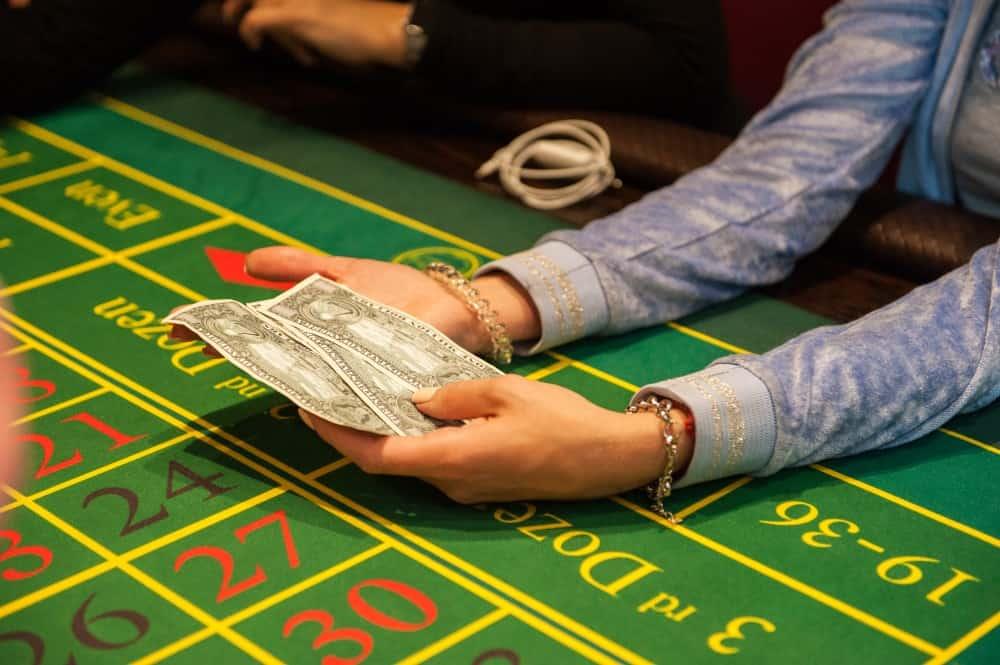 En person sitter vid kasinobordet och håller pengar