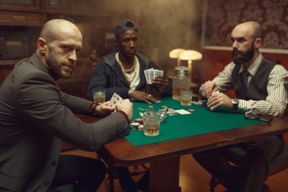Pokerspelare sitter vid bordet med korsade ben